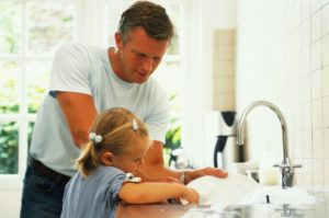 Man and young girl washing dishes together in a clean new kitchen.